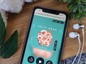 """Hörbuch """"Cinder&Ella"""" wiedergegeben auf einem Smartphone mit beiliegenden Kopfhörern"""