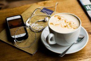 Kaffee mit iPhone, Kopfhörern und Notizheft auf einem Holztisch