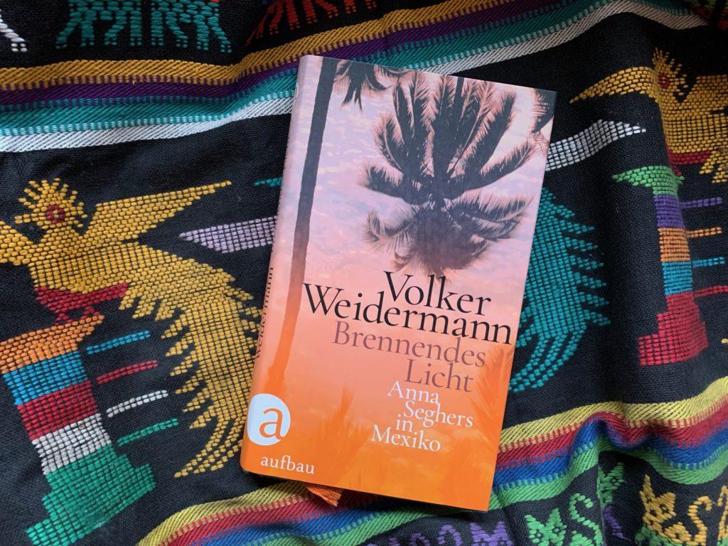 """Buchcover von Volker Weidermann """"Brennendes Licht. Anna Seghers in Mexiko"""", drapiert auf einer bunten mexikanischen Decke"""