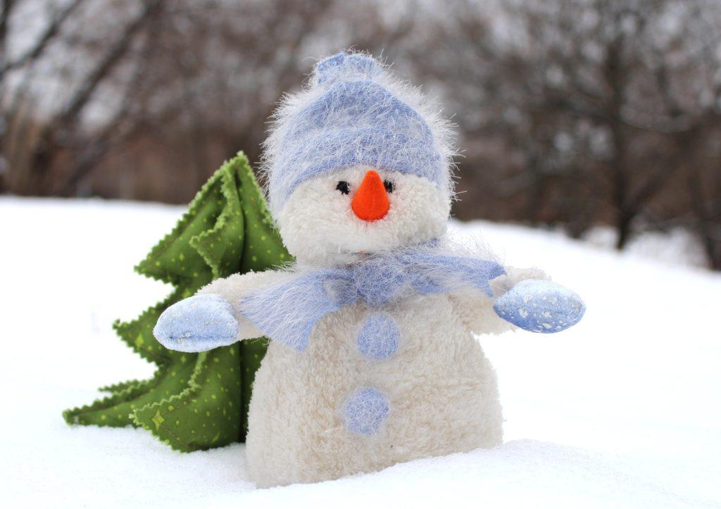 Schneemann im Schnee vor einer kleinen Tanne