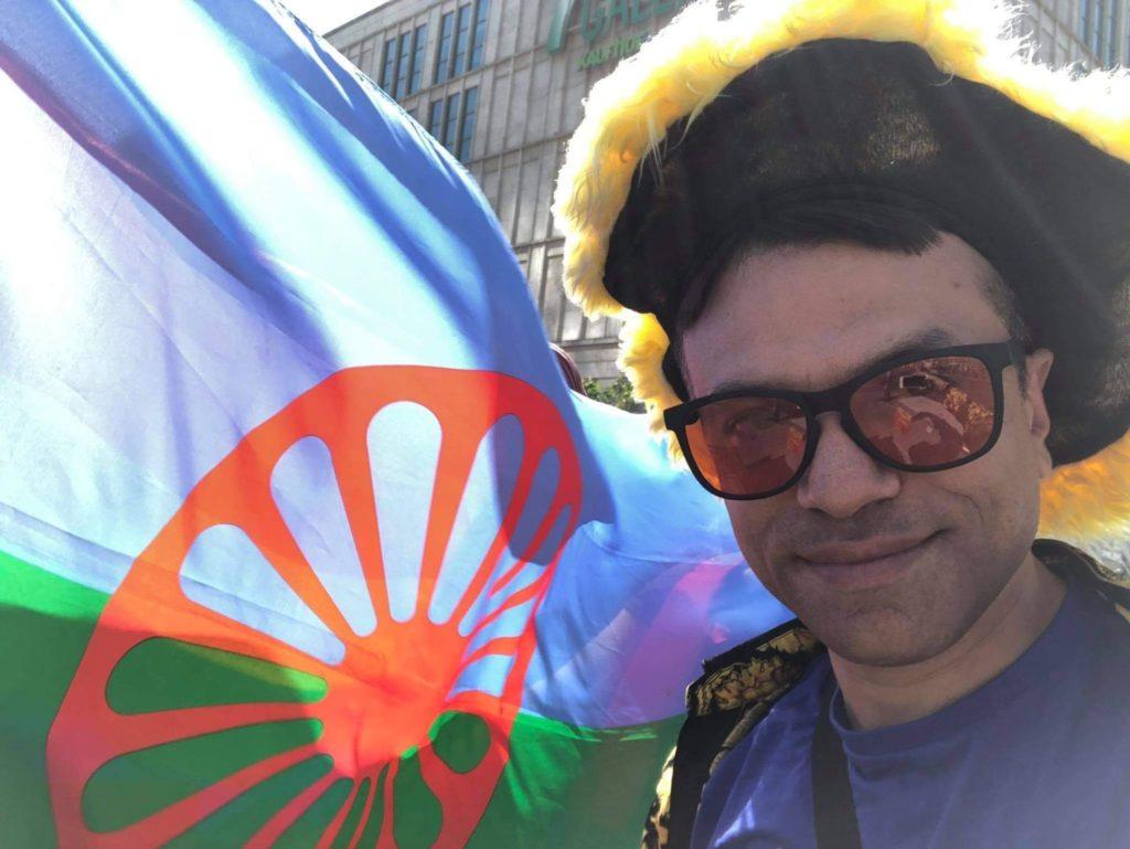 Der Roma-Aktivist Hamze Bytyci, bekleidet mit Hut und Sonnenbrille, lächelnd vor der Flagge der Roma.