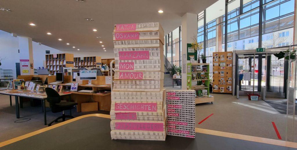 """Nachbau des Covers von """"Marzahn, mon amour"""" mit aussortierten Büchern. Auf dem Buchcover ist ein Hochhaus zu sehen."""